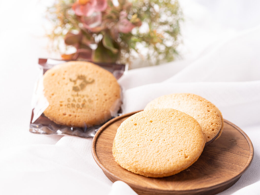 CROWNサンドクッキー。 CACAO CROWNオリジナルのミルクチョコレートをサクサク感にこだわり焼き上げたラングドシャクッキーで挟みました。